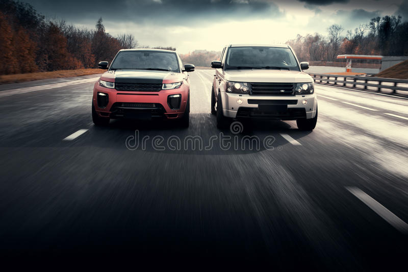 Cars Land Rover Range Rover drive on asphalt city road at autumn sunny daytime royalty free stock images