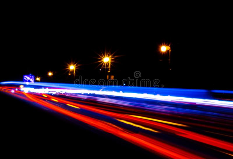 Cars light trails on a curved highway at night. Night traffic trails. Motion blur. Night city road with traffic headlight motion. Cityscape. Light up road by stock photos