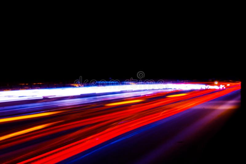Cars light trails on a curved highway at night. Night traffic trails. Motion blur. Night city road with traffic headlight motion. Cityscape. Light up road by royalty free stock photography