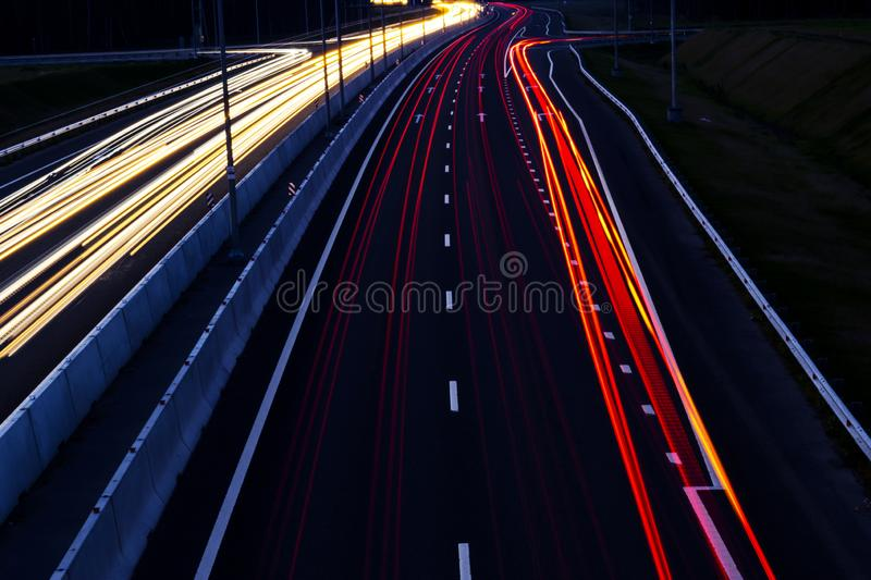 Cars light trails on a curved highway at night. Night traffic trails. Motion blur. Night city road with traffic headlight motion. royalty free stock photography