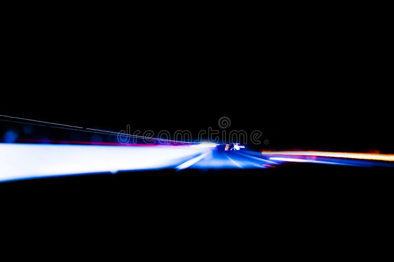 Cars light trails on a curved highway at night. Night traffic trails. Motion blur. Night city road with traffic headlight motion. Cityscape. Light up road by stock photography