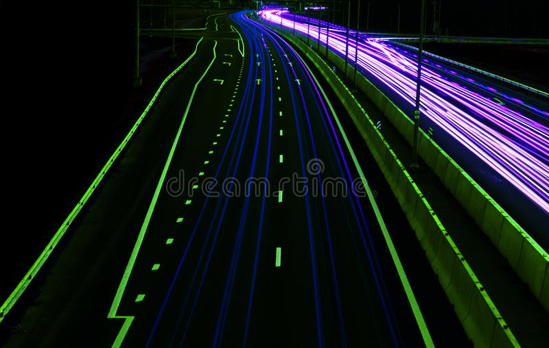 Cars light trails on a curved highway at night. Night traffic trails. Motion blur. Night city road with traffic headlight motion. Cityscape. Light up road by stock photo