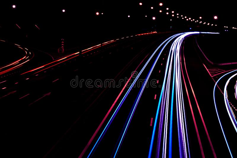 Cars light trails on a curved highway at night. Night traffic trails. Motion blur. Night city road with traffic headlight motion. Cityscape. Light up road by stock image