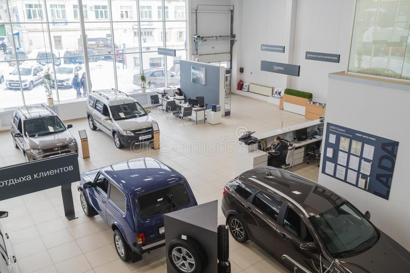 Cars, manager and customer in showroom of dealership AVTOVAZ named SeverAvto in Kirov city in 2018. Top view. Kirov, Russia - March 06, 2018: Cars, manager and stock photography