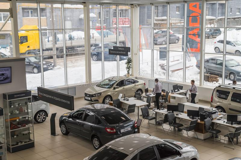 Cars, manager and customer in showroom of dealership AVTOVAZ named SeverAvto in Kirov city in 2018. Top view. Kirov, Russia - March 06, 2018: Cars, manager and royalty free stock photography