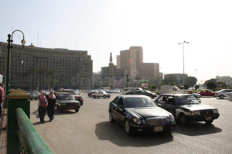 Cars, Mogamma building in tahrir downtown Cairo Egypt. Man crossing the street and the famous Mogamma building in tahrir downtown Cairo Egypt and the Mogamma stock photography