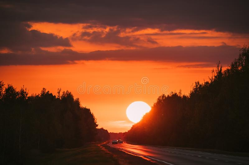 Cars In Motion On Road, Freeway. Asphalt Motorway Highway Against Background Of Big Sunset Sun. Travel Trip Concept. Sunshine Above Road royalty free stock images