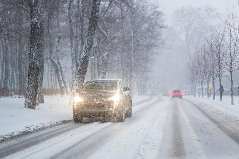 Cars moving on slippery snowy road at city street during heavy snowfall at evening in winter . Traffic obstacle due blizzard and stock image