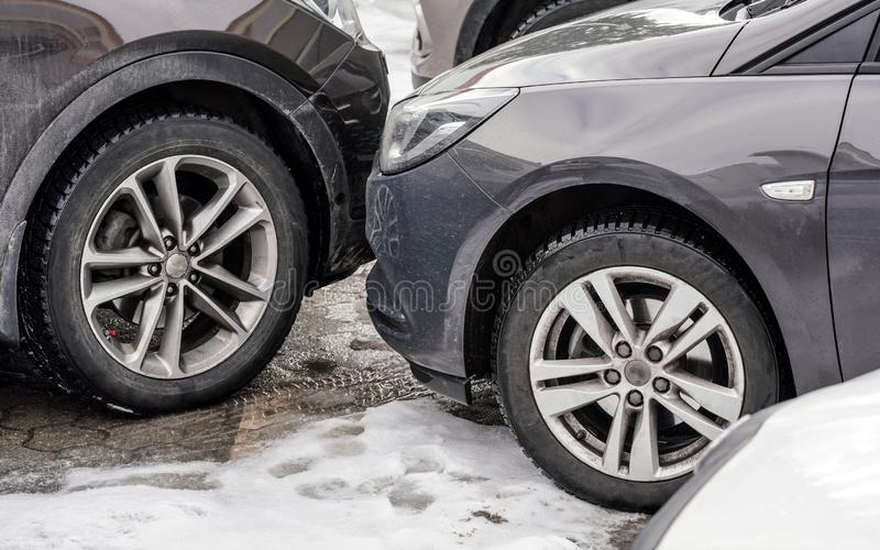 Cars parked with bumpers close to each other, detail on dirty front and tires at snow covered ground.  stock photos