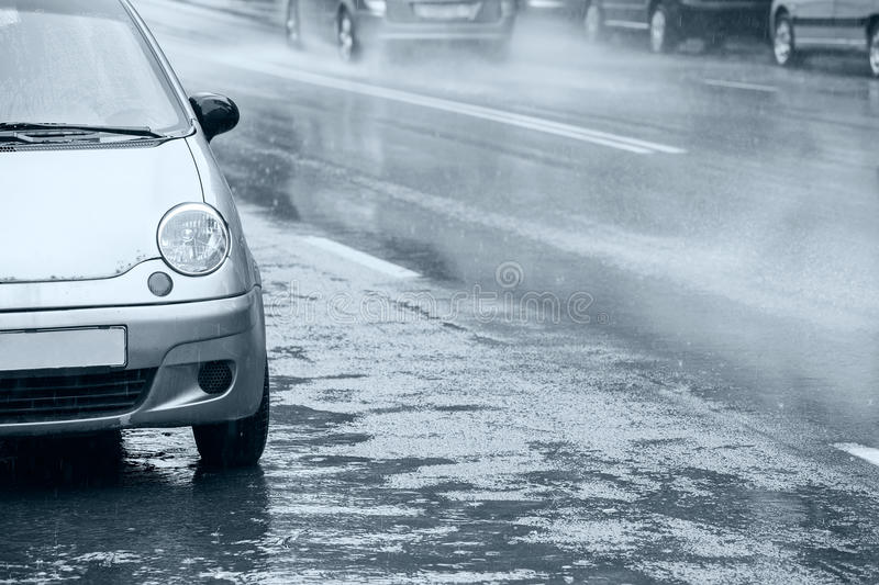 Cars parked in downpour. Water splashes in puddles on asphalt road stock images