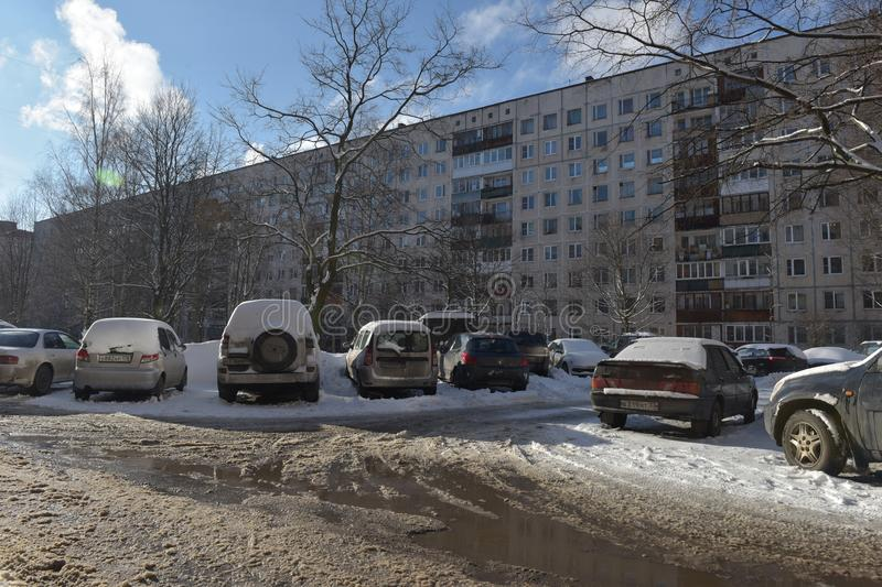Cars parked in front of an apartment block house in a residential area of the city in winter stock image