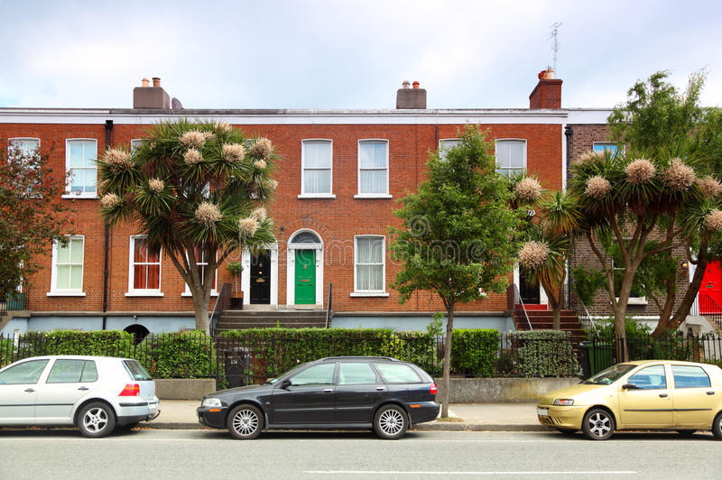 Cars parked near brick house on street in Dublin. Cars parked near two-story red brick house on street in Dublin, Ireland royalty free stock photography