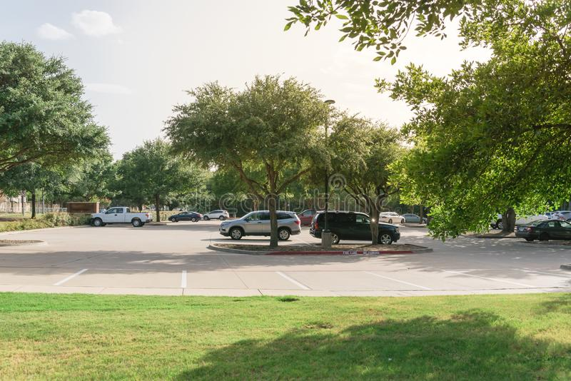 Shady public parking lot in Texas, USA. Cars parked under the tree shade at large public parking in Coppell, Texas, USA stock images