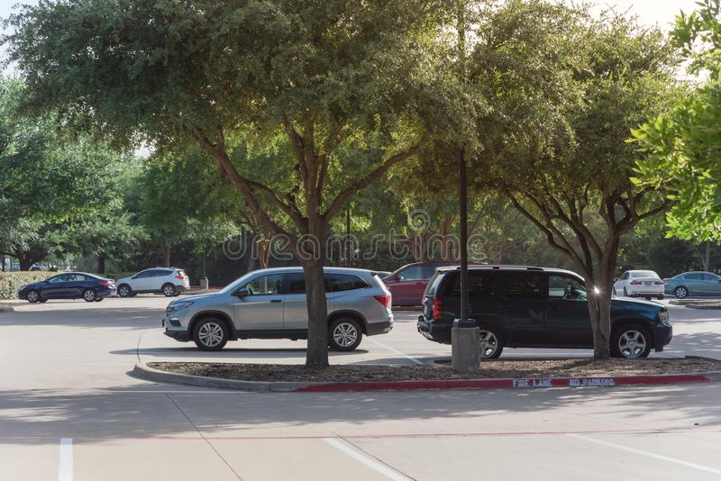 Shady public parking lot in Texas, USA. Cars parked under the tree shade at large public parking in Coppell, Texas, USA royalty free stock image