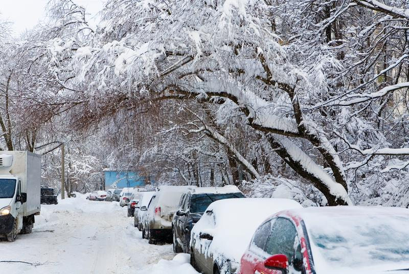 Cars are parked in the yard. Snowfall in Russia royalty free stock photo