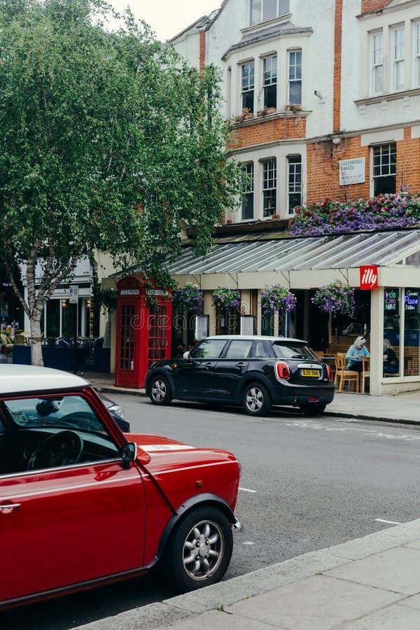 Cars, parkerad nära Le Cochonnet eatery på Lauderdale Road i London royaltyfri fotografi