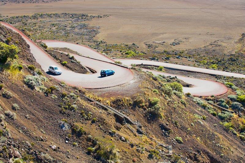 Cars pass by the road across Plaine des Sables at 2260 m above sea level near Piton de la Fournaise volcano. stock images