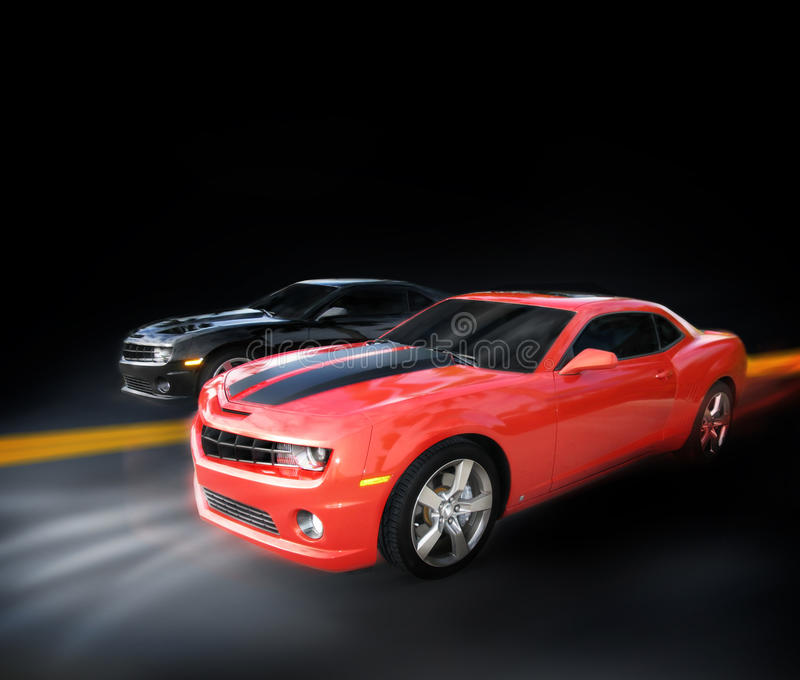 Cars racing. Two Chevrolet autos (Camaros) race down a dark highway