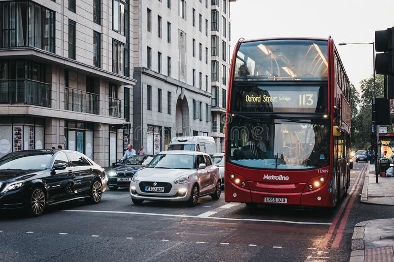 Cars and a red double decker bus number 113 towards Oxford Stree royalty free stock image