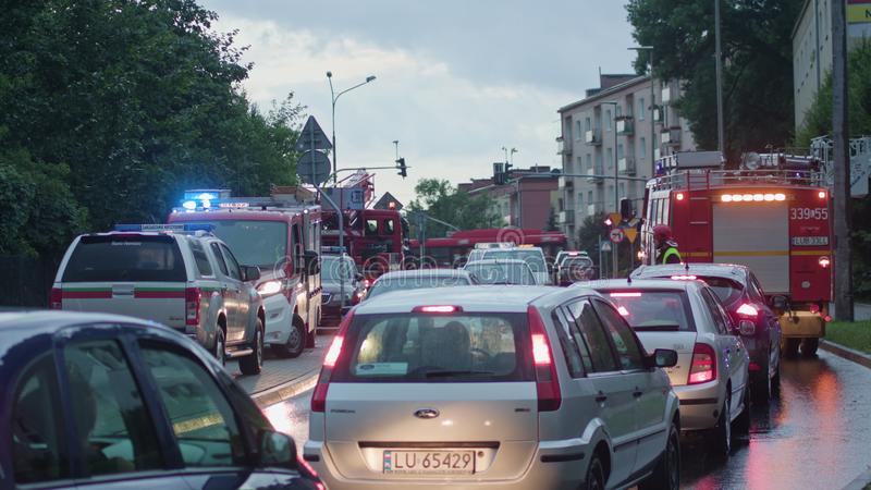 Cars Running with Lights On in the Rain. Lublin, poland - July 2017: Cars running with lights on in the rain. Firefighters regulating traffic. City scene. Long royalty free stock image