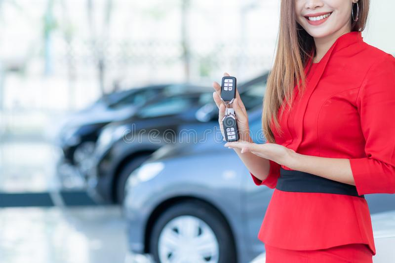 Cars For Sale, Beautiful Asian woman or car salesman Stand holding a new car remote key in the showroom royalty free stock photo