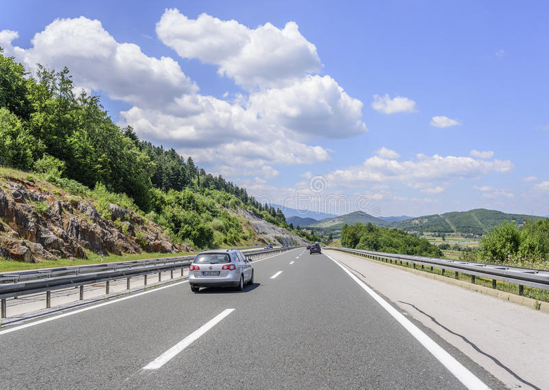 Cars speeding on the Autobahn among mountain scenery. OTOCHAC, CROATIA - JULY 16, 2017: Cars speeding on the Autobahn among mountain scenery royalty free stock photography