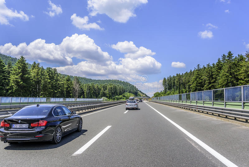 Cars speeding on the Autobahn among mountain scenery. OTOCHAC, CROATIA - JULY 16, 2017: Cars speeding on the Autobahn among mountain scenery royalty free stock images