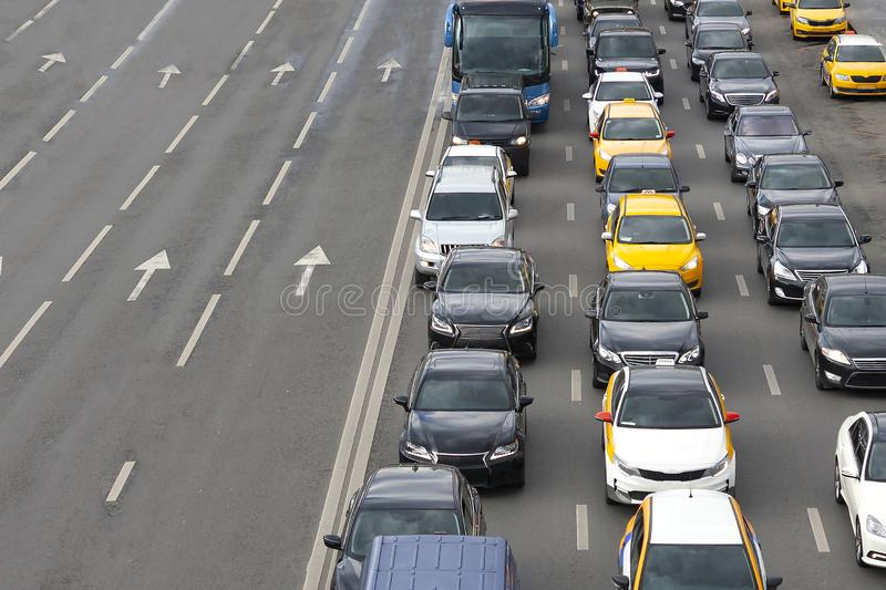 Cars standing in a traffic jam on one side of a busy highway. Transportation rush hour in a city. royalty free stock images