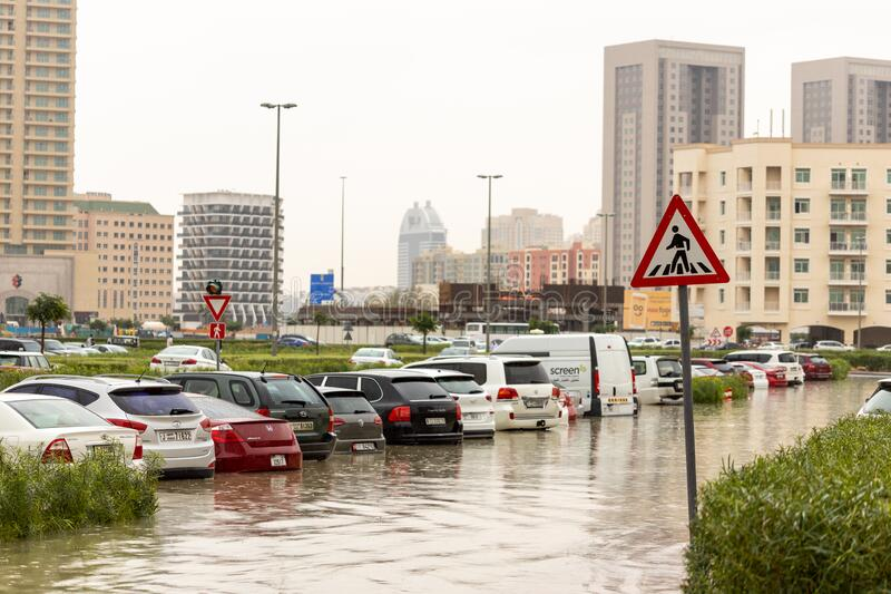DUBAI, UAE - CIRCA 2020: Cars stuck in water in a flooded parking lot after heavy in rain in Dubai stock photography