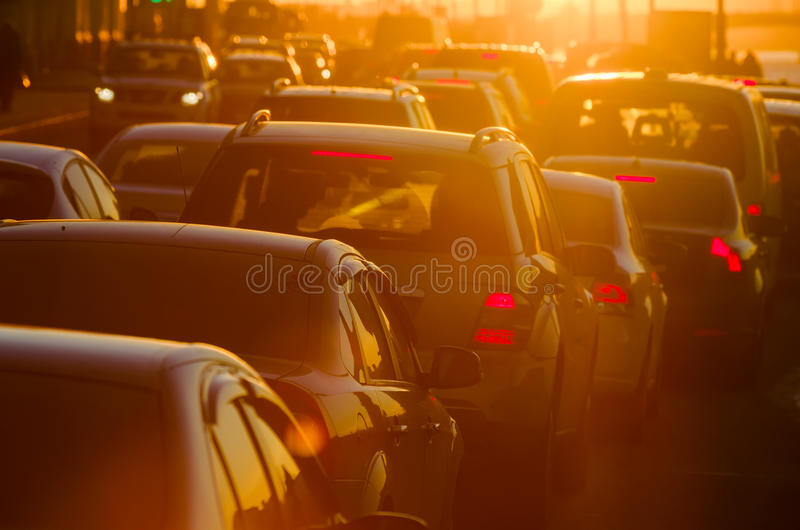 Cars are in traffic jam during a beautiful golden sunset. stock photo