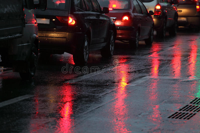 Cars in traffic jam on wet road. At rainy city evening royalty free stock photos