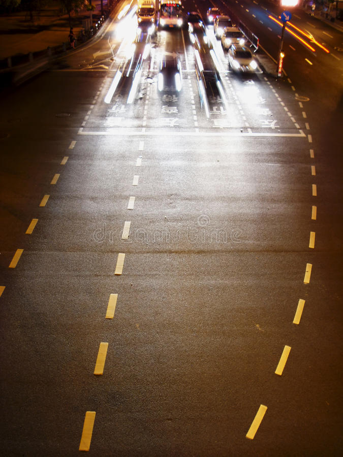 Cars at the traffic lights at night. Cars starting at the traffic lights of an urban road at night stock image