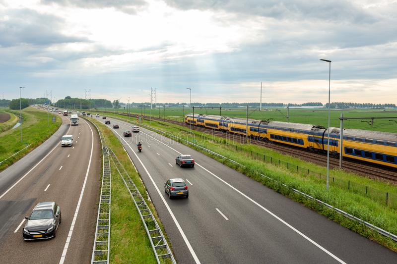 Cars and train on the A44 highway near Abbenes. stock photo