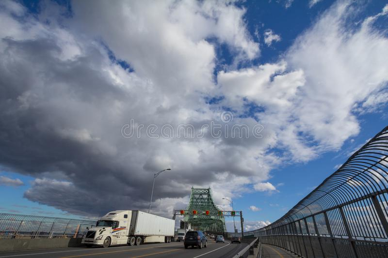 Cars & truck traffic on the highway of Jacques Cartier bridge, in the direction to Montreal. royalty free stock image