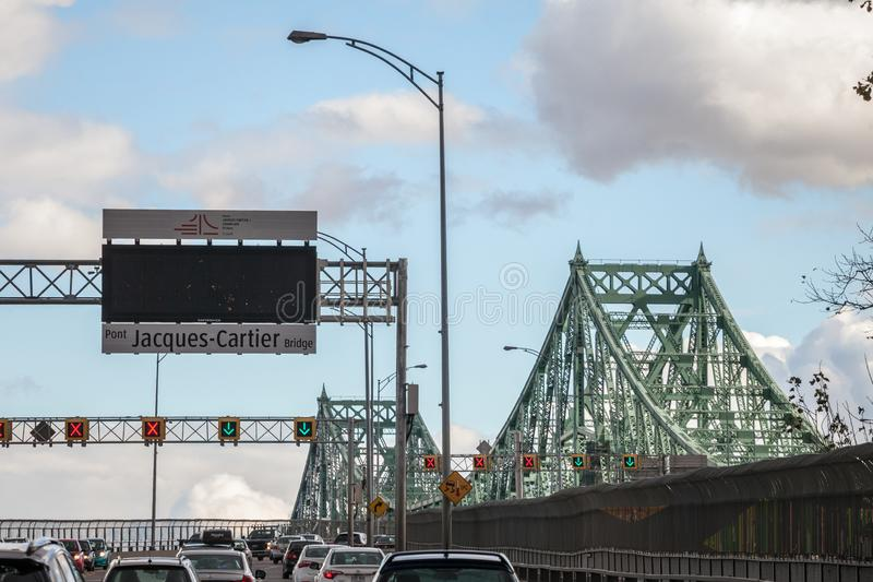 Cars & truck traffic on the highway of Jacques Cartier bridge with its logo, in the direction to Montreal. royalty free stock photos