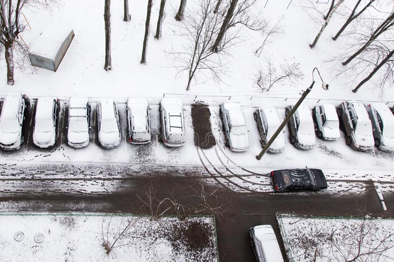 Cars under snow on a parking. First snow concept stock image