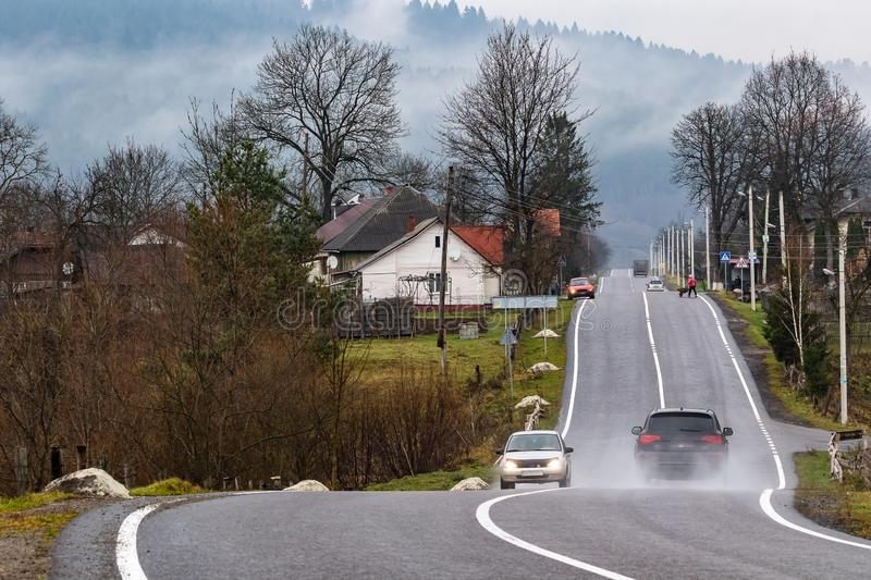 Cars on a winding mountain road in a small village. The tops of high mountains are hidden by clouds. royalty free stock photography