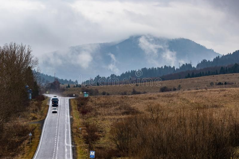 Cars on a winding mountain road in a small village. The tops of high mountains are hidden by clouds. Fog. Autumn landscape. Panoramic view stock image