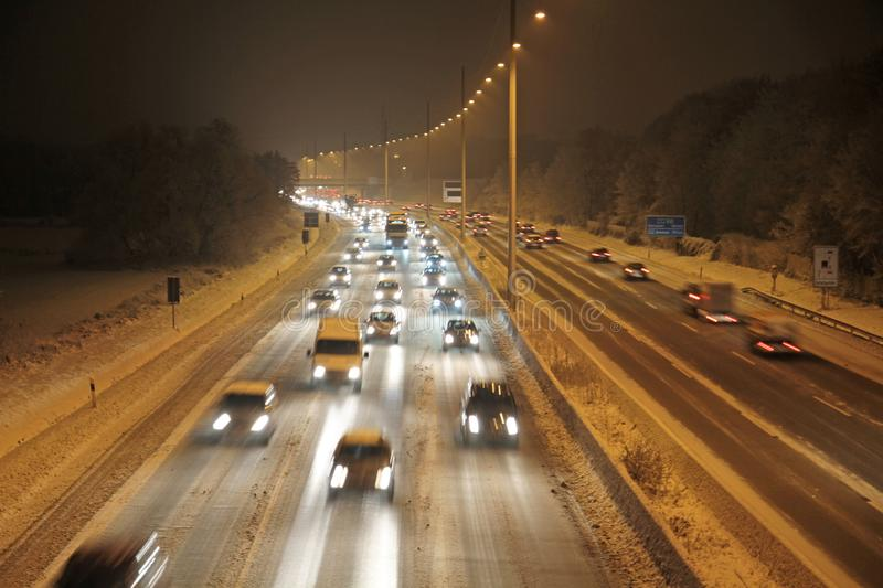 Winter_highway. Cars on winterly highway at night royalty free stock photography