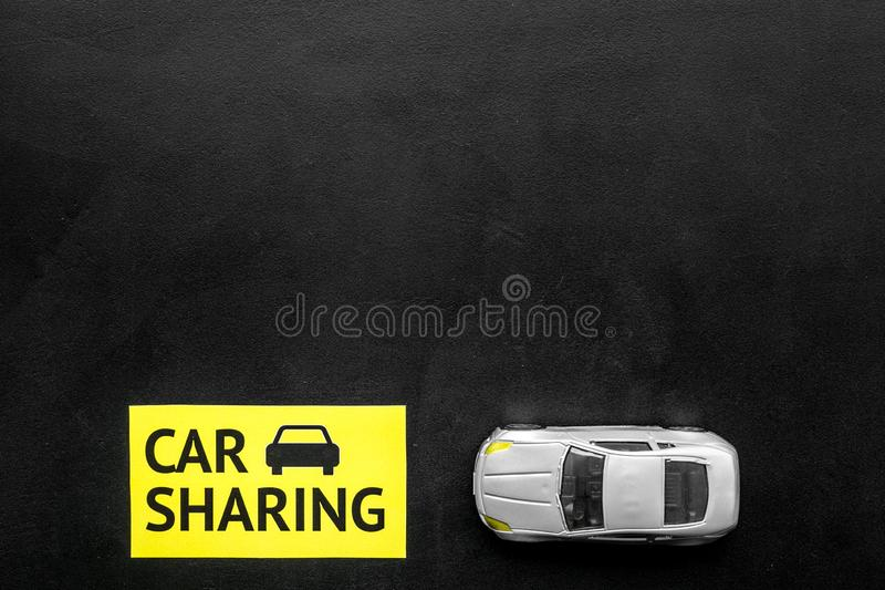 Carsharing concept. Toy car near text car sharing on black background top view space for text. Carsharing concept. Toy car near text car sharing on black royalty free stock image