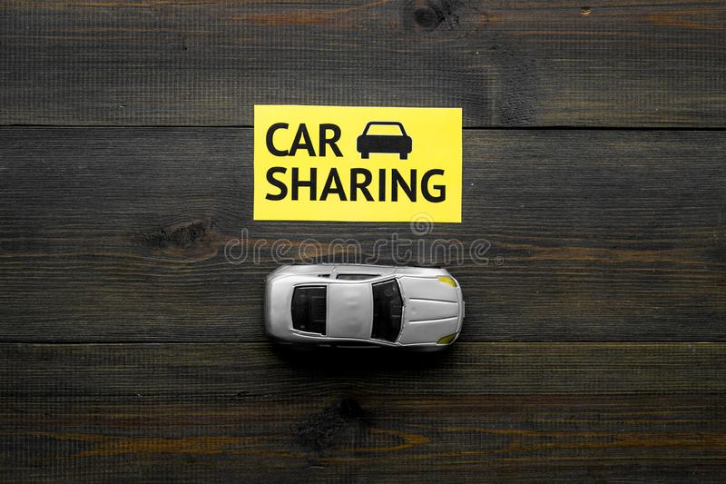 Carsharing concept. Toy car near text car sharing on dark wooden background top view space for text. Carsharing concept. Toy car near text car sharing on dark stock photography