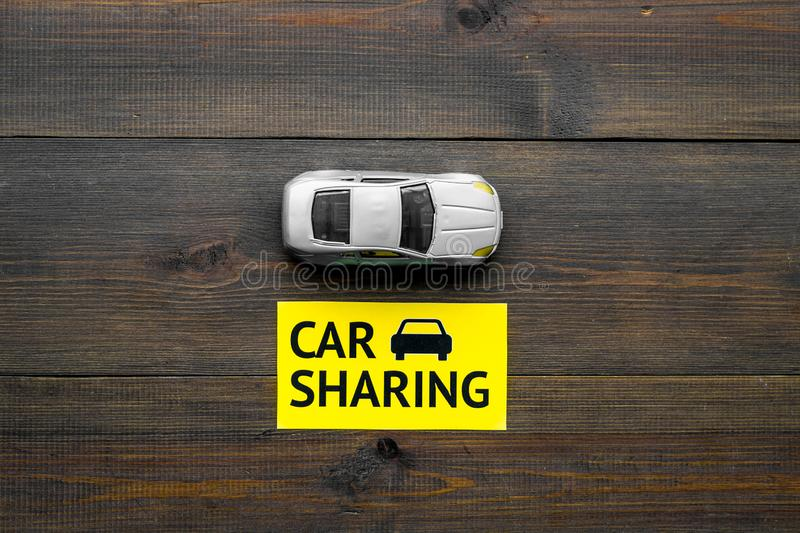 Carsharing concept. Toy car near text car sharing on dark wooden background top view copy space. Carsharing concept. Toy car near text car sharing on dark wooden stock photos