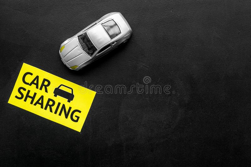 Carsharing concept. Toy car near text car sharing on black background top view space for text. Carsharing concept. Toy car near text car sharing on black royalty free stock photo