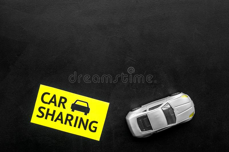 Carsharing concept. Toy car near text car sharing on black background top view space for text. Carsharing concept. Toy car near text car sharing on black stock photo