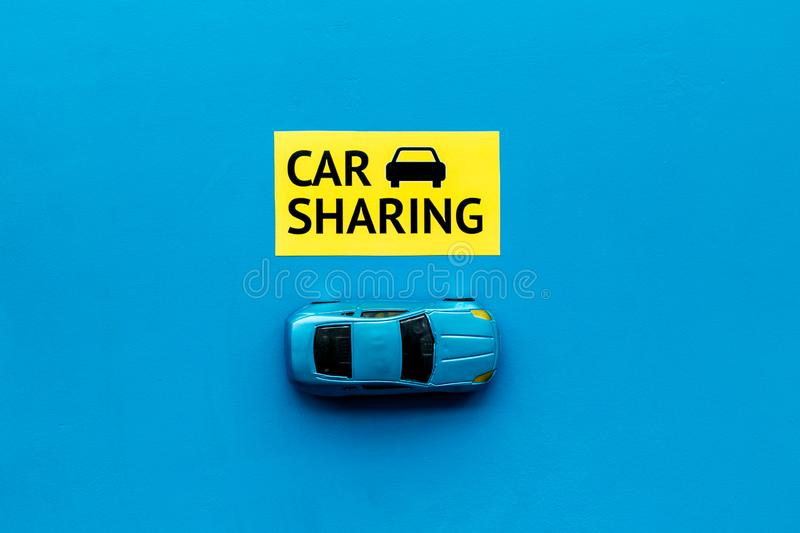Carsharing concept. Toy car near text car sharing on blue background top view copy space. Carsharing concept. Toy car near text car sharing on blue background royalty free stock photo