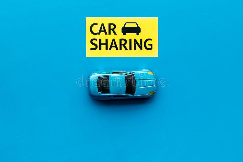 Carsharing concept. Toy car near text car sharing on blue background top view copy space. Carsharing concept. Toy car near text car sharing on blue background royalty free stock photos
