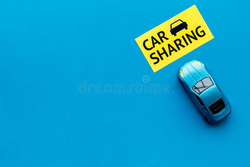Carsharing concept. Toy car near text car sharing on blue background top view copy space. Carsharing concept. Toy car near text car sharing on blue background stock photography