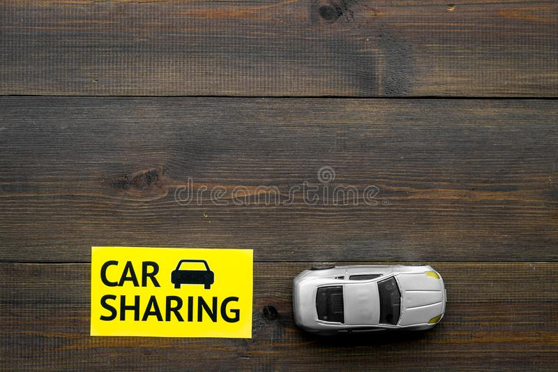 Carsharing concept. Toy car near text car sharing on dark wooden background top view copy space. Carsharing concept. Toy car near text car sharing on dark wooden stock image