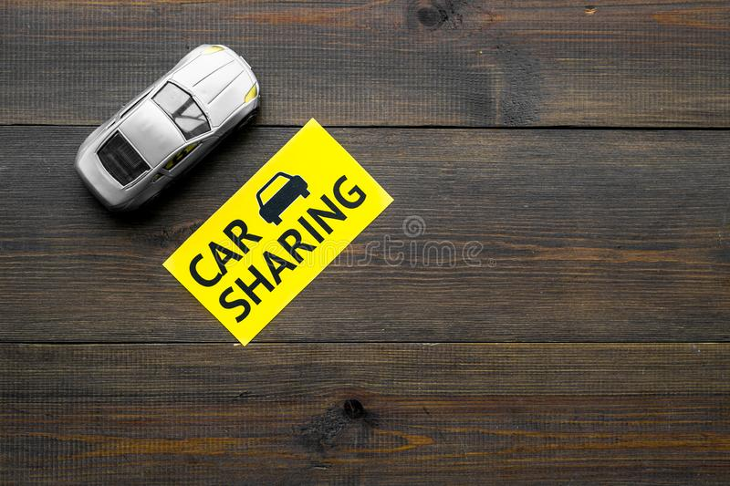 Carsharing concept. Toy car near text car sharing on dark wooden background top view copy space. Carsharing concept. Toy car near text car sharing on dark wooden royalty free stock photography