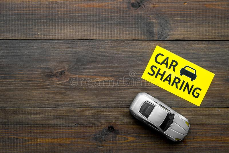 Carsharing concept. Toy car near text car sharing on dark wooden background top view copy space. Carsharing concept. Toy car near text car sharing on dark wooden royalty free stock photos